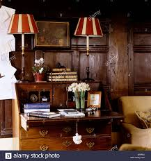 striped lshades on wooden writing bureau in country