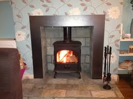 modern wood burning stove installed with metal custom surround