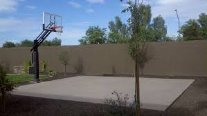 this concrete playing area in the backyard sits at the end of the