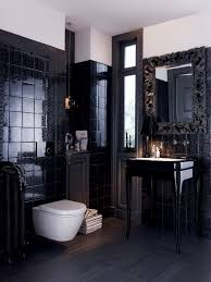 the sleek detailed black tile walls make for a powder room that