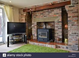 brick fireplace with wood burning stove and flatscreen television