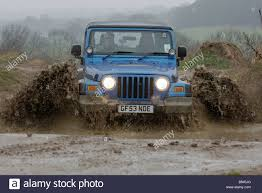 rally jeep wrangler jeep wrangler splashes through deep water off road stock photo