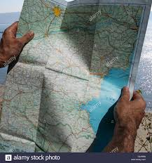 Map Paper Hands Holding Old Paper Road Map Up To A Beach Background Stock