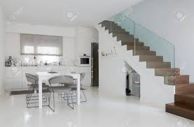 white kitchen and dining room with white epoxy floor and wooden