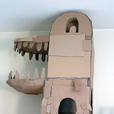 human builds a dragon shaped cardboard house for his cat in order