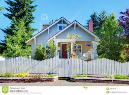 grey small cute house with white fence and gates stock images