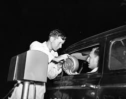 attendant bud grote hands an in car speaker to thomas speakman at