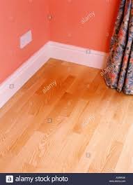 Red Laminate Flooring Corner Of Room With Laminate Wood Floor And White Skirting Board