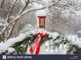 winter garden birds feed at a red christmas garden birdfeeder on a