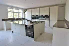 contemporary island kitchen high gloss handleless kitchen with s shaped island corian worktop