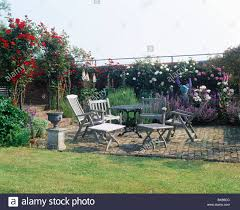 wooden table and chairs on brick paved patio in walled garden with