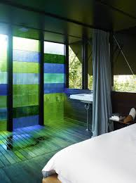 cottage with colored glass walls and pre existing trees
