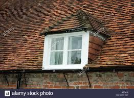 dormer window in roof slope of english cottage hampshire uk stock
