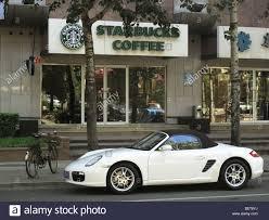 white porsche boxster convertible a white porsche convertible car in front of a starbucks coffee