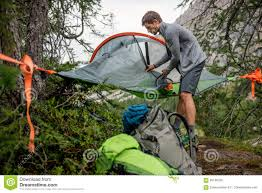 man preparing hanging tent camping mosquito net in overcast day