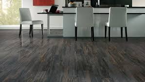 grey wooden laminate flooring with white island and chairs also