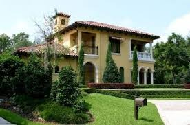 upscale yellow spanish style stucco home with well manicured
