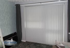 wide vertical blind in white fabric covering patio doors harmony