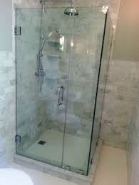 glass shower enclosure with half wall beside toilet for guest