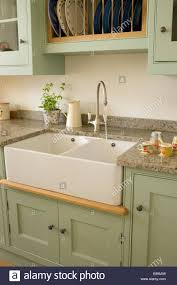 sink units for kitchens chrome tap above double belfast sink in pale green units in