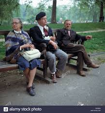 bench spectacles seventies people three persons sitting on a park bench at the
