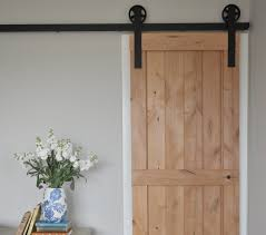 Interior Door Hanging Interior Un Varnish Sliding Barn Door Hanging On Black Iron Rails