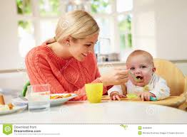 High Sitting Chair Mother Feeding Baby Sitting In High Chair At Mealtime Stock Images
