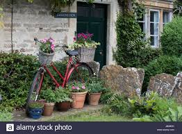 A Garden Of Flowers by Old Bicycle Baskets And Wicker Full Of Flowers In The Front Garden