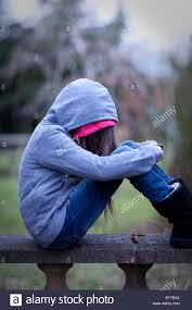 images of sad girl sad girl in hoodie with face hidden sitting alone on a wall in