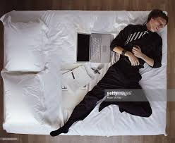 young man in suit sleeping on bed next to laptop overhead view
