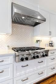 white tile backsplash kitchen steel blue cabinetry white quartz countertops white chevron