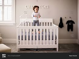 Off White Baby Crib by Toddler Boy Jumping In Crib Stock Photo Offset