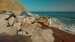 tilting shot of a mediterranean volcanic beach with red sand and