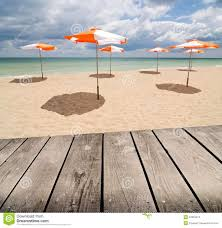 umbrellas on the beach and empty wooden deck table stock images