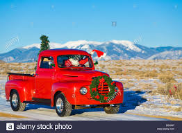 Vintage Ford Pickup Truck - santa driving a vintage red ford pick up truck down a snowcovered
