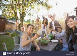 portrait of friends toasting drinks at backyard barbecue stock