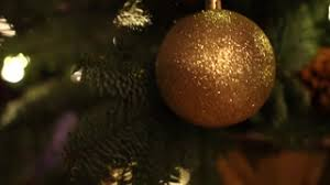 a christmas tree decorated with golden glitter christmas tree ball