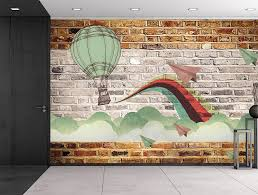 faux brick wall pattern with painted mural whimsical hot air baloon and paper airplanes design breaking