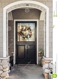 black front door of a home seen through an arch stock photo