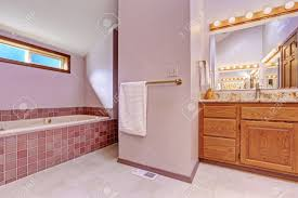 bathroom interior in light pink tone with tile trim bath tub