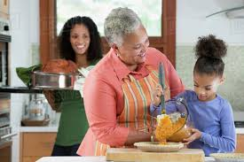 three generations of black women cooking in kitchen stock photo