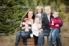 large family christmas card photo in christmas tree farm stock