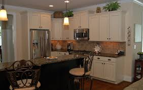kitchens with black appliances and white cabinets tin backsplash