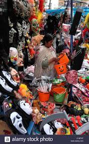 aymara lady selling masks for halloween in street market la paz