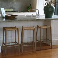 light brown wooden backless stools with long legs plus white