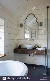 slab sink basin resting on slab of timber in bathroom with walls lined white
