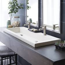 small trough bathroom sink with two faucets
