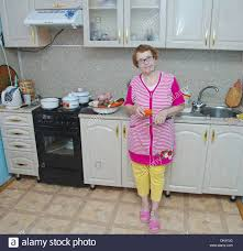 knives in the kitchen european elderly woman in the kitchen is a full length with a
