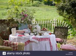 lawn in country garden with vase of summer flowers on table with