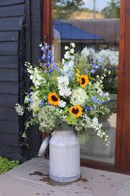 milk churns filled with delphiniums hydrangeas and sunflowers by